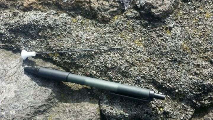 One of two blow darts that struck pedestrians on San Francisco's Golden Gate Bridge on Friday is seen next to a pen.