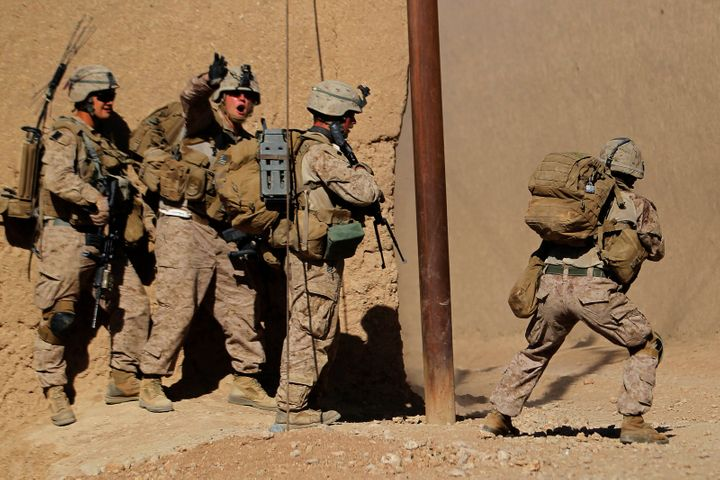 U.S. Marine Sgt. Thomas Brennan shouts to his comrades to keep out of the line of fire from Taliban insurgents during a firef