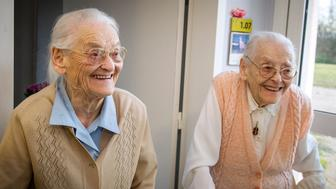 Centenary twins, Simone Thiot (L) and Paulette Olivier (R), smile inside the Ephad 'Les Bois Blancs' in Onzain, central France, on February 11, 2016.  The twins, birth name Lamolie, were born on January 30, 1912 at 11 o'clock at the address Impasse 'du coteau' in Limeray, a few kilometres from Amboise. The two sisters aged 104 years are believed to be the two oldest twins in the world. / AFP / GUILLAUME SOUVANT        (Photo credit should read GUILLAUME SOUVANT/AFP/Getty Images)