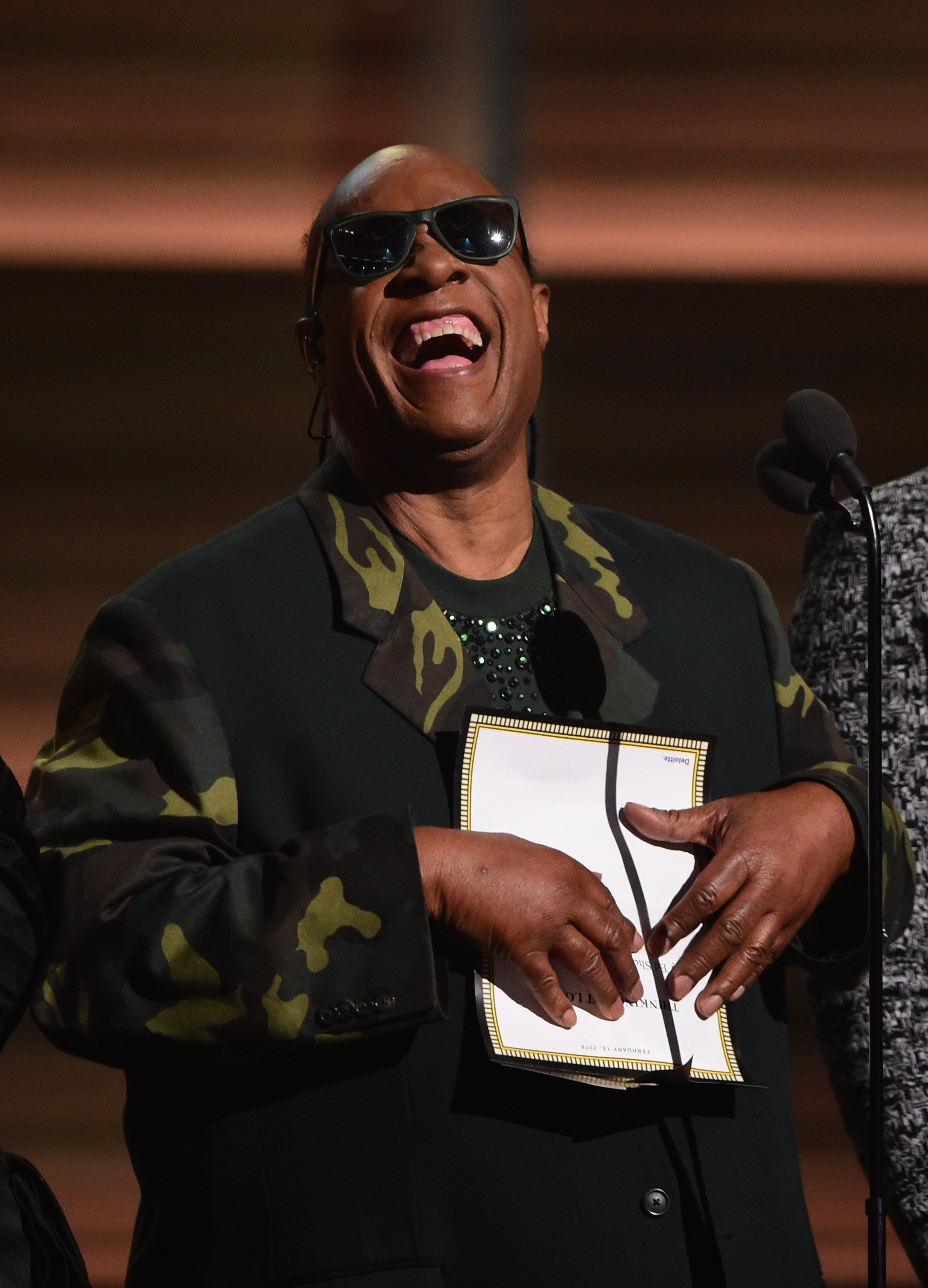 Musician  Stevie Wonder presents the Song of the Year on stage during the 58th Annual Grammy music Awards in Los Angeles February 15, 2016.  AFP PHOTO/  ROBYN BECK / AFP / ROBYN BECK        (Photo credit should read ROBYN BECK/AFP/Getty Images)