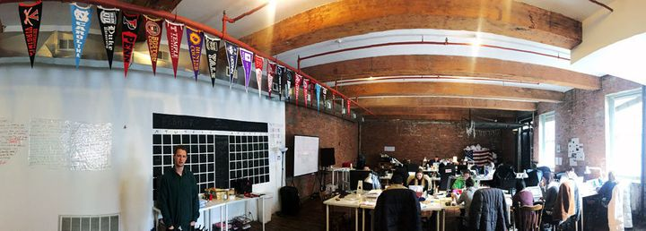 Jack Rivlin, co-founder of The Tab, at left, stands in their Brooklynoffice below pennants representing the campuses wh