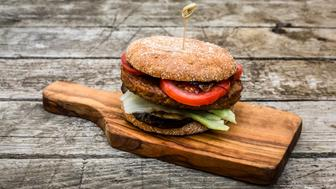 Homemade veggie burger with aubergine, lettuce, tomato and onion on chopping board