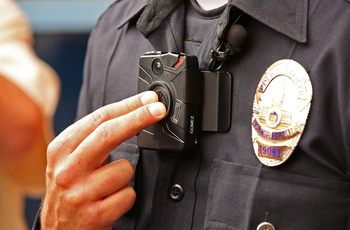 Los Angeles Police Officer Jim Stover demonstrates how an officer turns on the new LAPD body camera during a press conference