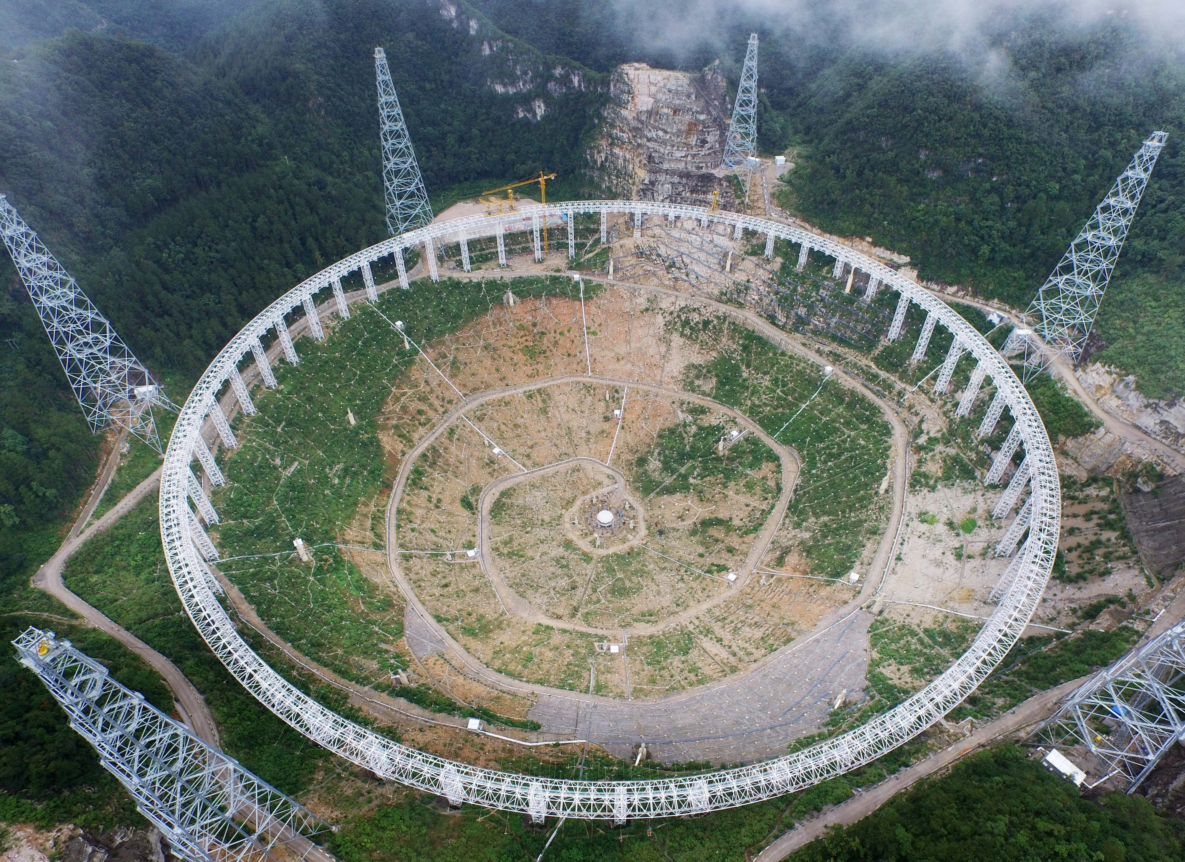 QIANNAN BUYEI AND MIAO AUTONOMOUS PREFECTURE, CHINA - JULY 28:  (CHINA OUT) Aerial view of the Five hundred meter Aperture Spherical Telescope (FAST) built in mountains on July 28, 2015 in Pingtang County, Qiannan Buyei and Miao Autonomous Prefecture, Guizhou province of China. The FAST would be used mainly for capturing radio signals in the universe. With a diameter of 500 meters it would be the world's largest radio telescope when completed in September, 2016.  (Photo by ChinaFotoPress/ChinaFotoPress via Getty Images)