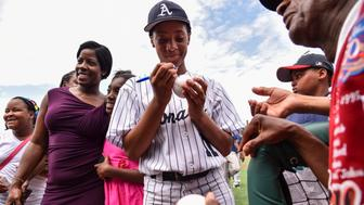 WASHINGTON, DC - JUNE 19: Anderson Monarchs' Mo'ne Davis, center, autographs a baseball headed for the Negro League Baseball Museum in Baltimore after her game against the DC Knights at the Washington Nationals Youth Baseball Academy on June 19, 2015 in Washington, D.C. The Anderson Monarchs little league team from Philadelphia, is on a 20-city Civil Rights tour making a stop in D.C. to play the DC Knights. The team features Little League World Series pitcher Mo'ne Davis, the first African-American girl to play in the series. The Monarchs beat the Knights 14-3. (Photo by Ricky Carioti/The Washington Post via Getty Images)