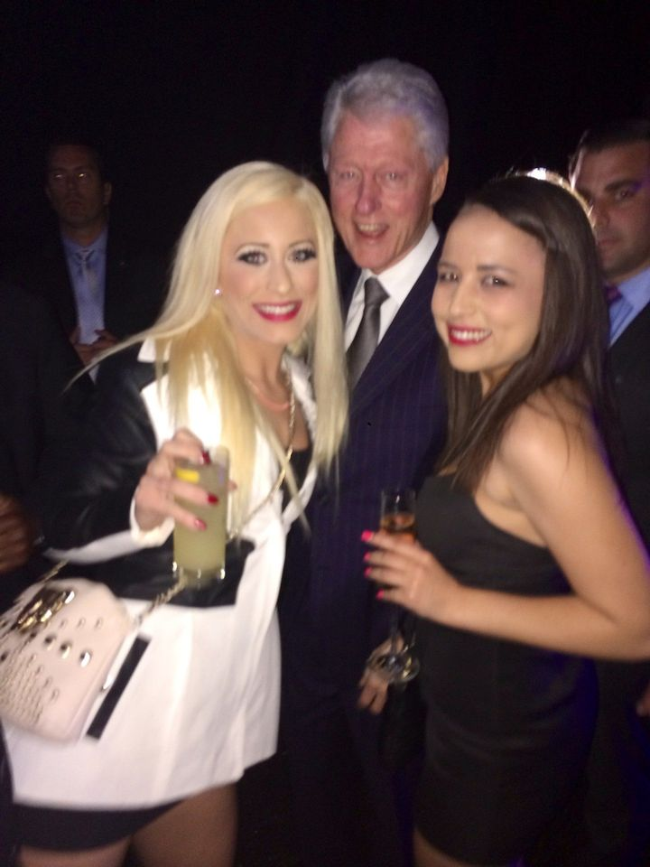 In this photo taken Feb. 28, 2014, Bill Clinton poses with Barbie Girl and Ava Adora, employees at the Moonlight Bunny Ranch