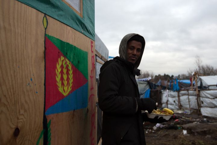 An Eritrean man eats lunch next to a shelter with the Eritrean flag in the camp known as the Jungle in Calais, France, i