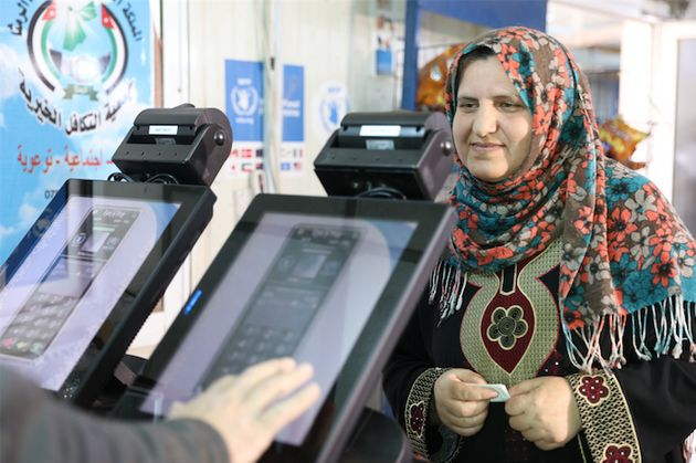 A Syrian refugee has her eyes scanned to pay for groceries at King Abdullah Park refugee camp...