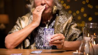 Close up of aged fortune teller reading tarot card meaning