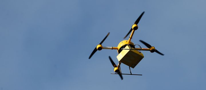 A quadcopter drone carrying a small parcel for delivery.