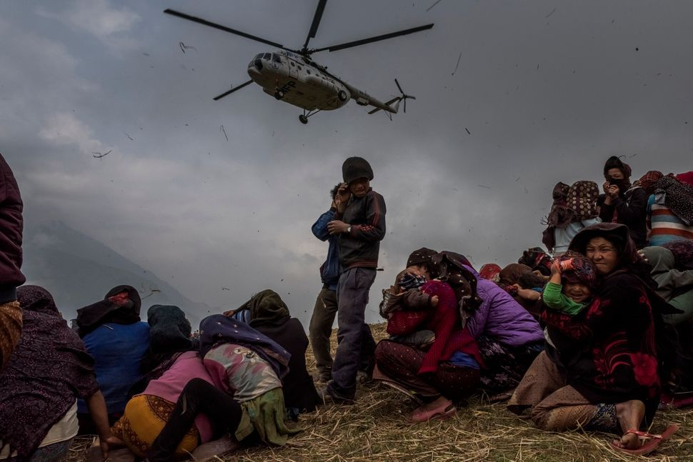 Nepalese villagers look on as they watch a helicopter picking up a medical team and dropping aid at the edge of a makeshift l
