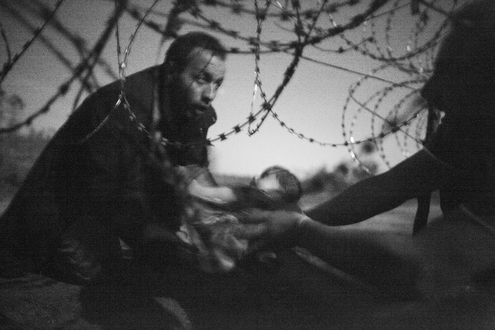 A man passes a baby through the fence at the Hungarian-Serbian border in Röszke, Hungary, 28 Aug. 2015.