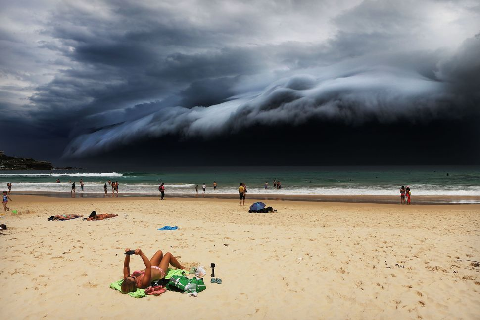 A woman sunbathing on Bondi Beach, Australia, is oblivious to the ominous shelf cloud approaching on Nov. 6, 2016.