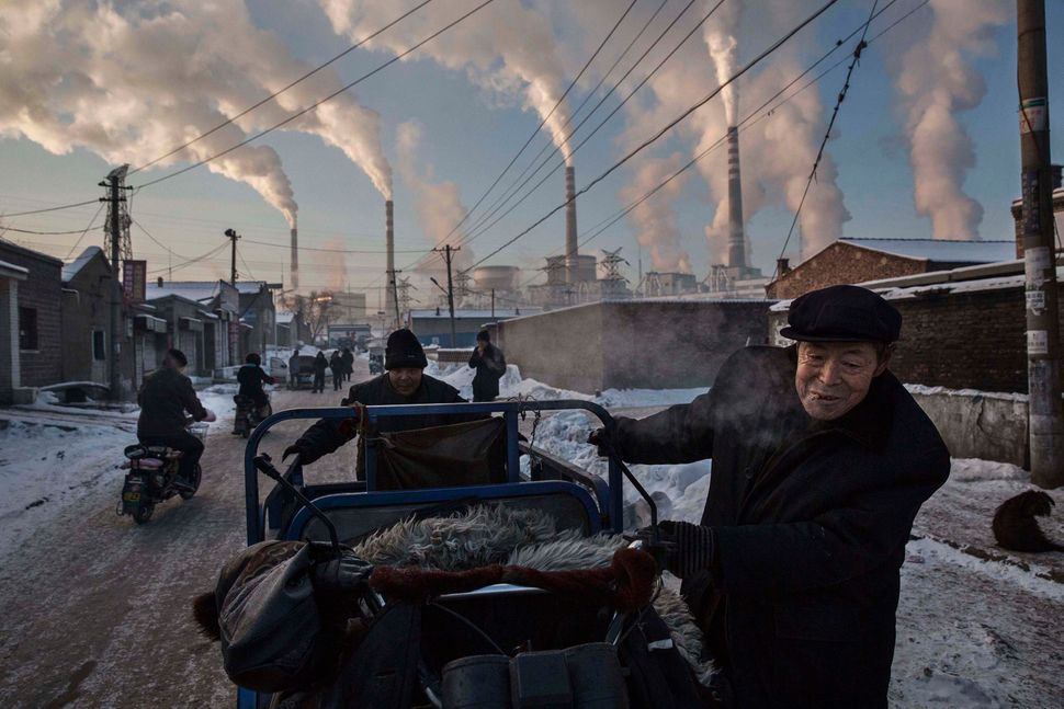 Chinese men pull a tricycle in a neighborhood next to a coal-fired power plant in Shanxi, China, on Nov. 26, 2015.