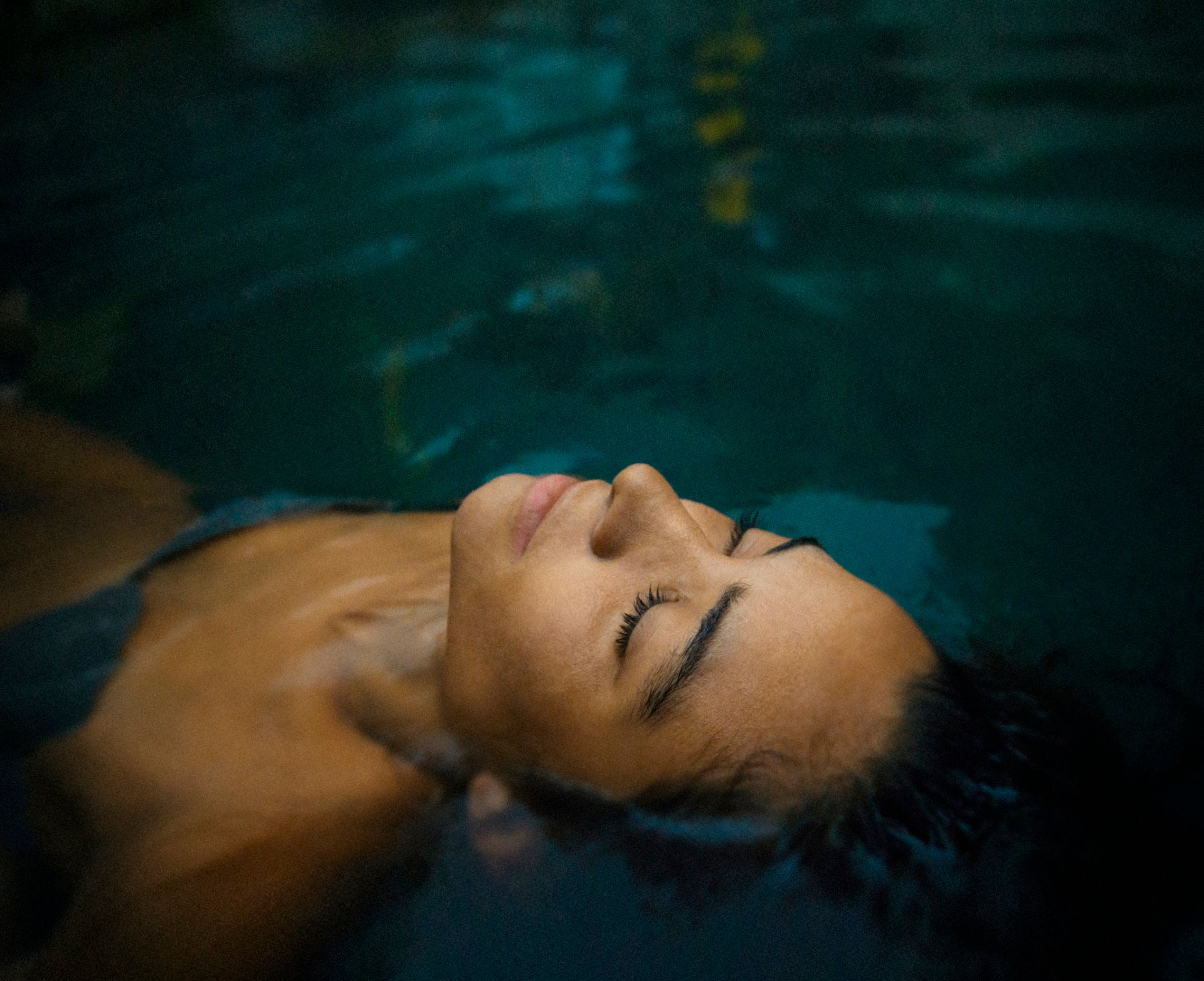 portrait of woman relaxing in outdoor hot spring, eyes closed, selective focus, soft evening light