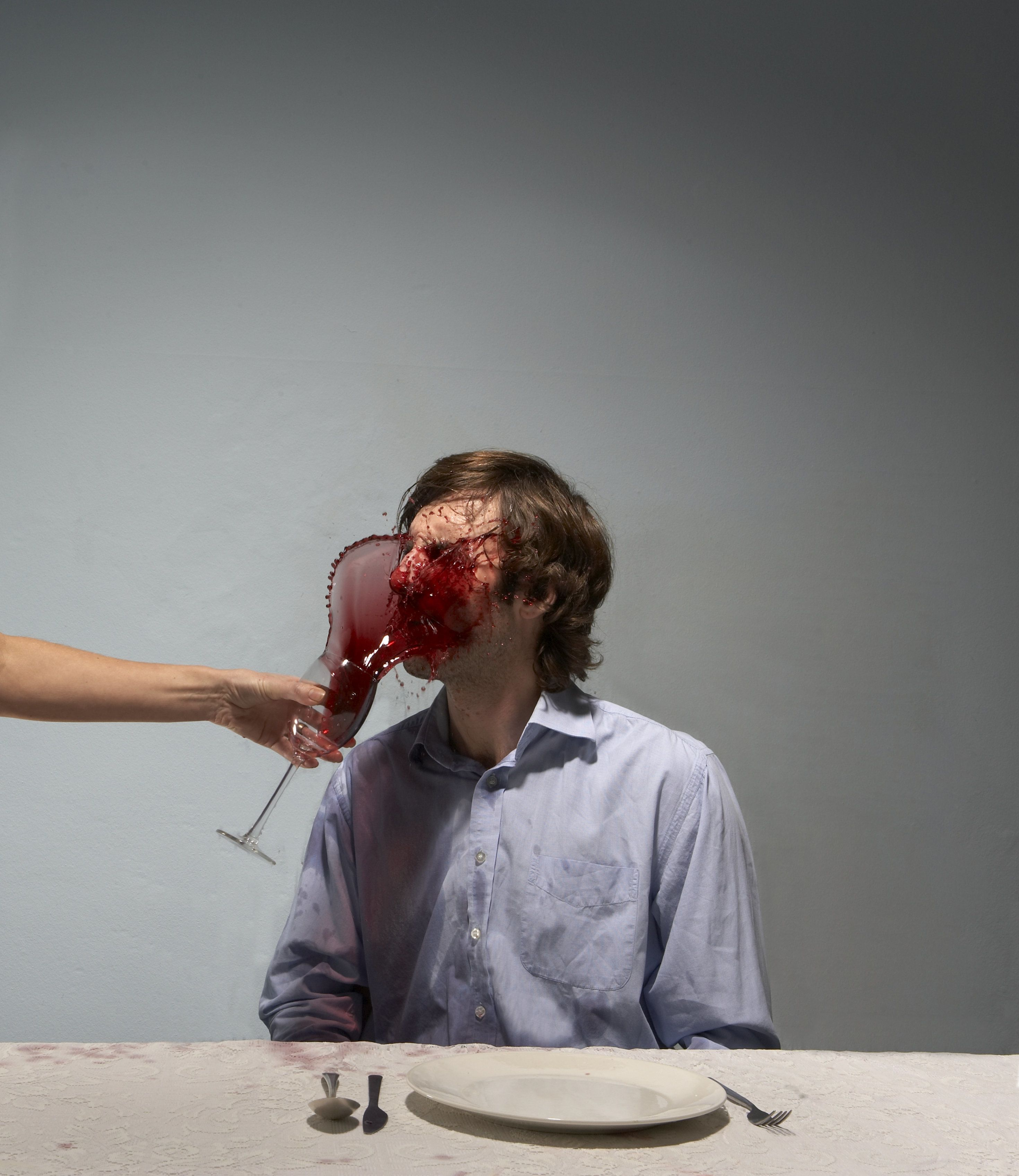 Woman throwing red wine in man's face