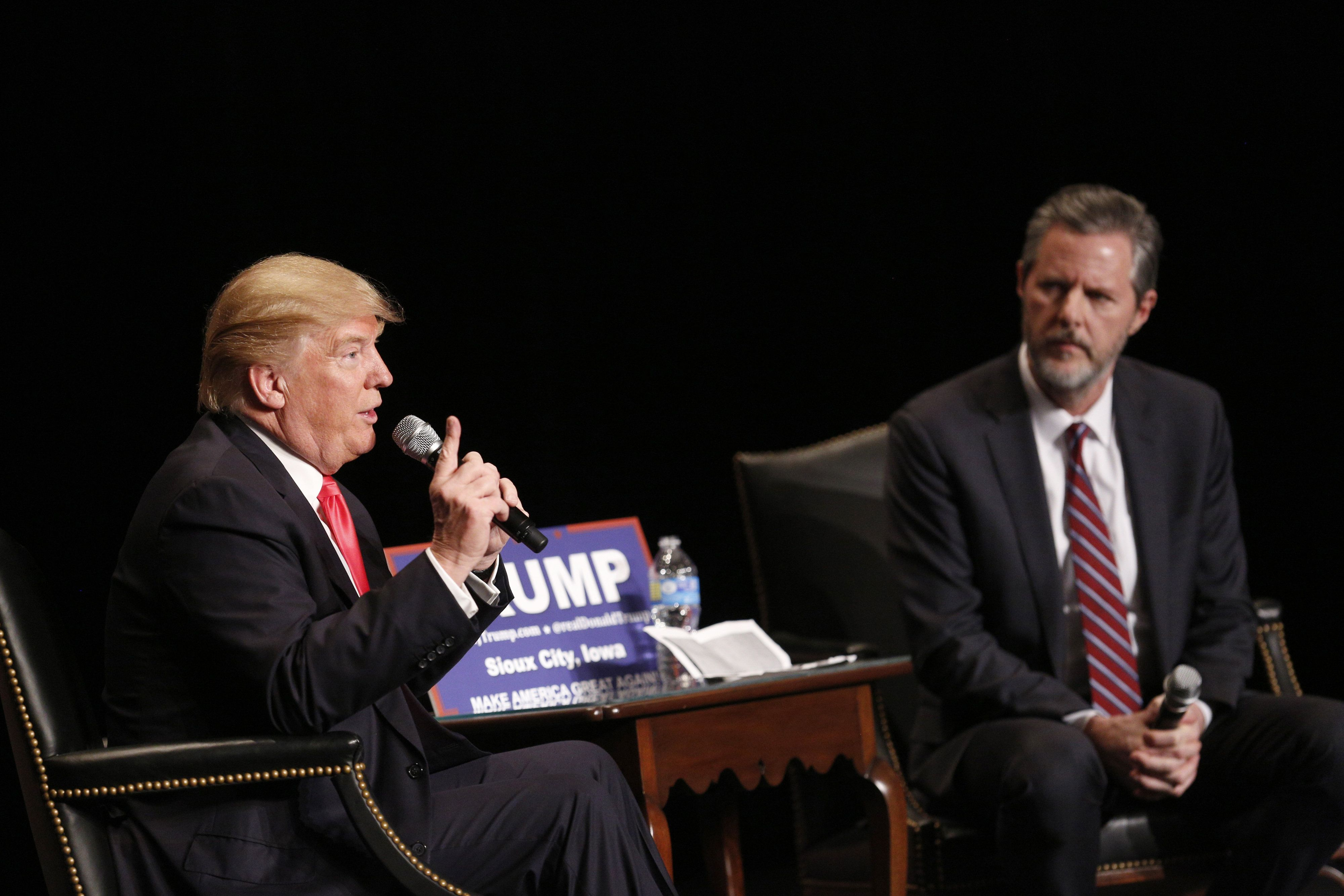 Jerry Falwell Jr. sits with Donald Trump during a campaign campaign event in January. Falwell, who has endorsed Trump, on Thu