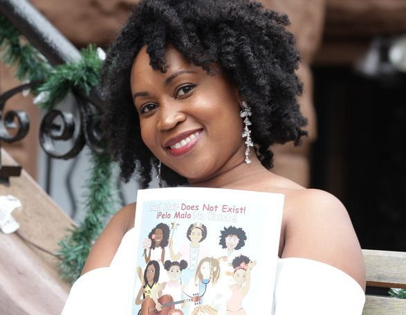 Sulma Arzu-Brown holding her book, <i>Bad Hair Does Not Exist!</i>