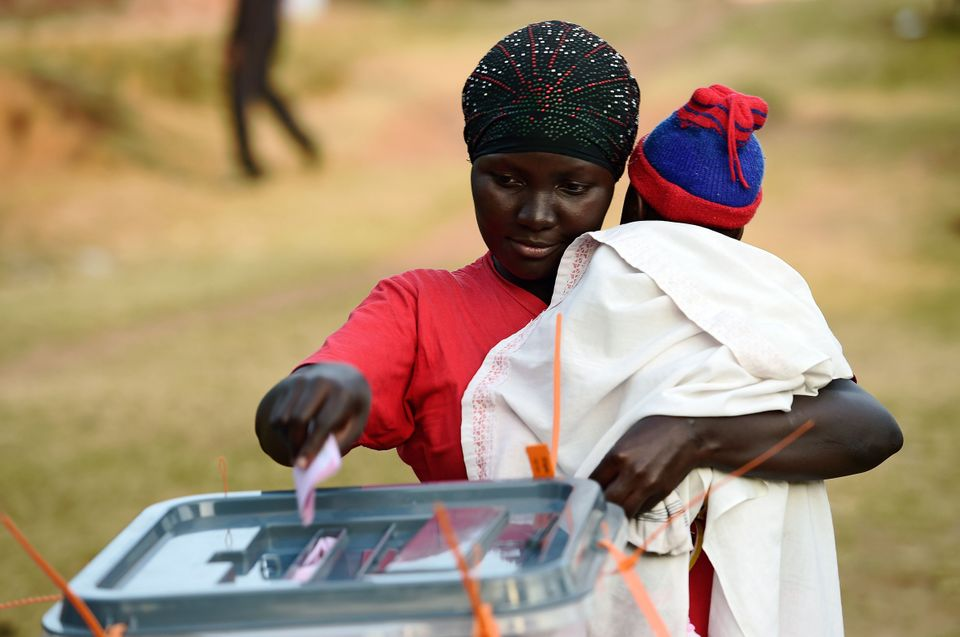 A woman holding her child casts her ballot during Uganda's national elections in Kampala on Feb. 18, 2016.