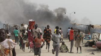 TOPSHOT - South Sudanese civilians flee fighting in an United Nations base in the northeastern town of Malakal on February 18, 2016, where gunmen opened fire on civilians sheltering inside killing at least five people.  Gunfire broke out in the base in Malakal in the northeast Upper Nile region on February 17, 2016 night, with clashes continuing on Thursday morning that left large plumes of smoke rising from burning tents in the camp which houses over 47,000 civilians.  / AFP / Justin LYNCH        (Photo credit should read JUSTIN LYNCH/AFP/Getty Images)