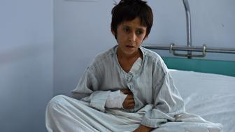 A wounded Afghan boy, survivor of the US airstrikes on the MSF Hospital in Kunduz, sits on his bed at the Italian aid organization, Emergency's hospital in Kabul on October 6, 2015.    Afghan forces called in a US air strike on a Kunduz hospital that killed 22 people, the top American commander in Afghanistan said October 5, 2015, after medical charity MSF branded the incident a war crime.  AFP PHOTO / Wakil Kohsar        (Photo credit should read WAKIL KOHSAR/AFP/Getty Images)
