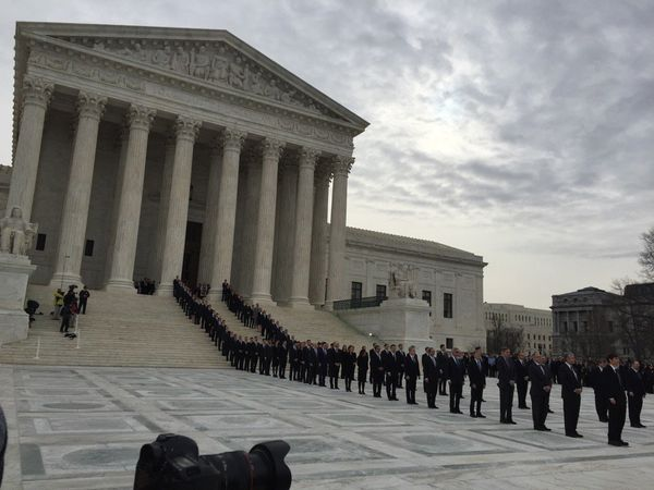 Supreme Court staff, clerks and former clerks line up on the plaza to await the arrival of Justice Antonin Scalia's casket.