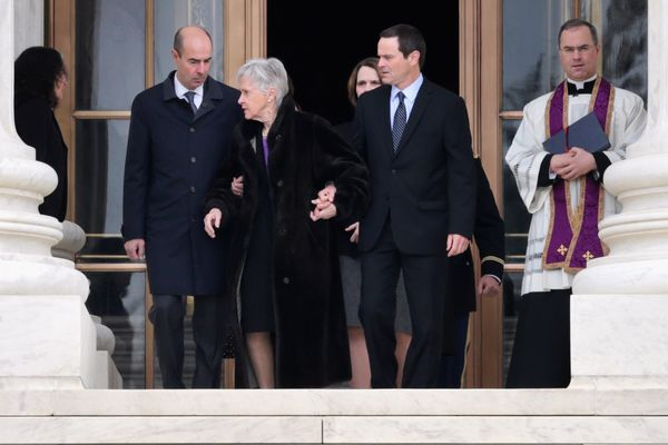 Maureen Scalia, center, widow of U.S. Supreme Court Associate Justice Antonin Scalia, is escorted by family members as she wa