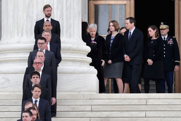 Maureen Scalia, center, widow of U.S. Supreme Court Associate Justice Antonin Scalia, waits on the portico of the court build