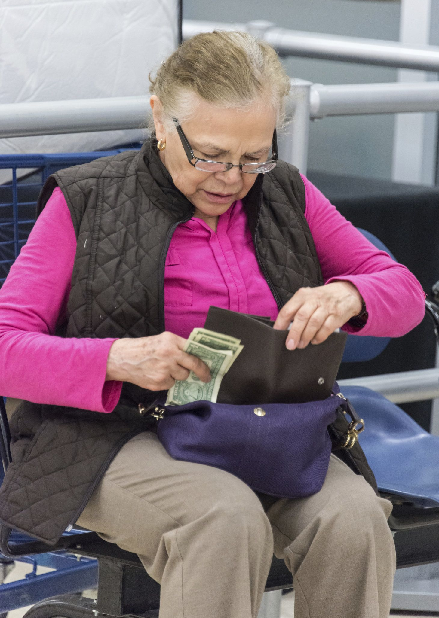 Old lady counting her money sitting at a bus station