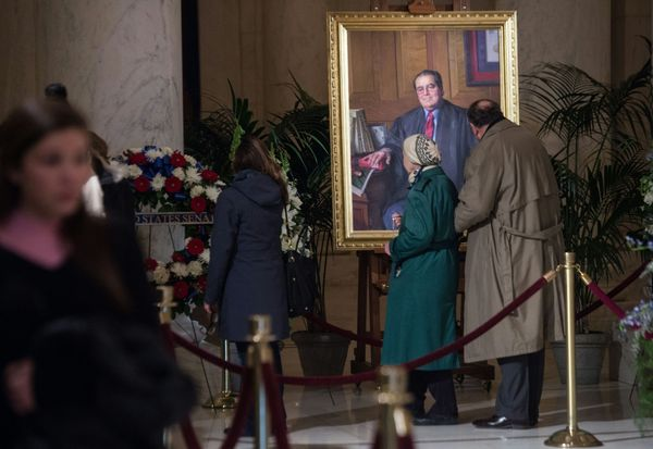 People look at a portrait of Supreme Court Justice Antonin Scalia in Washington, D.C., on Feb. 19, 2016, as he lies in repose