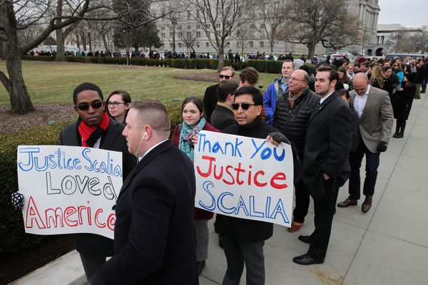 People hold signs of thanks and support while waiting in line to pay their respects to U.S. Supreme Court Associate Justice A