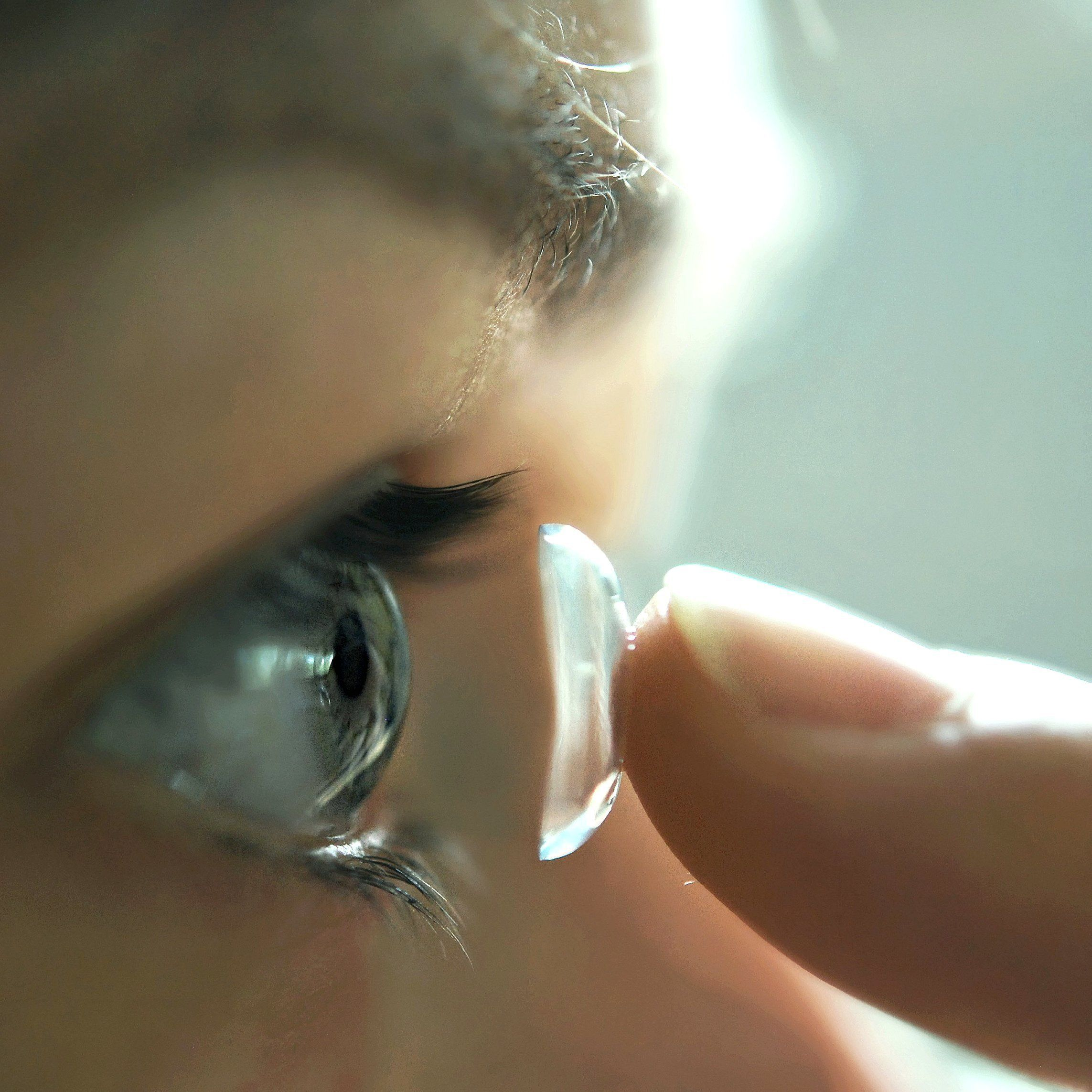 Close up of contact lens being put into eye.