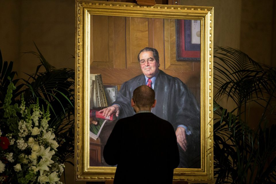 A mourner pays his respects in front of a portrait of Supreme Court Justice Antonin Scalia during a private visitation in the