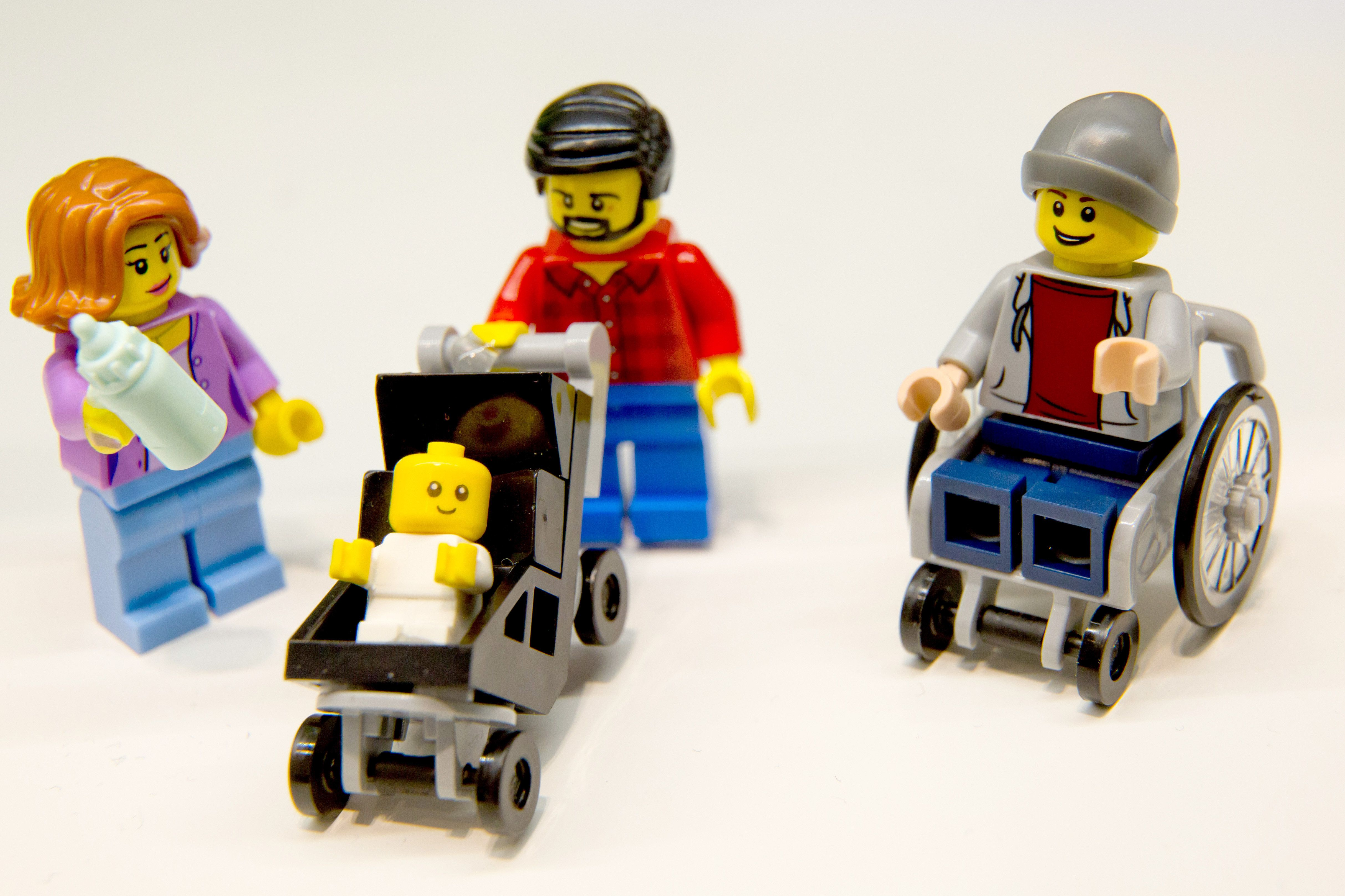 New LEGO minifigures, including a stay-at-home dad, working mom, baby in a stroller and young man in a wheelchair.