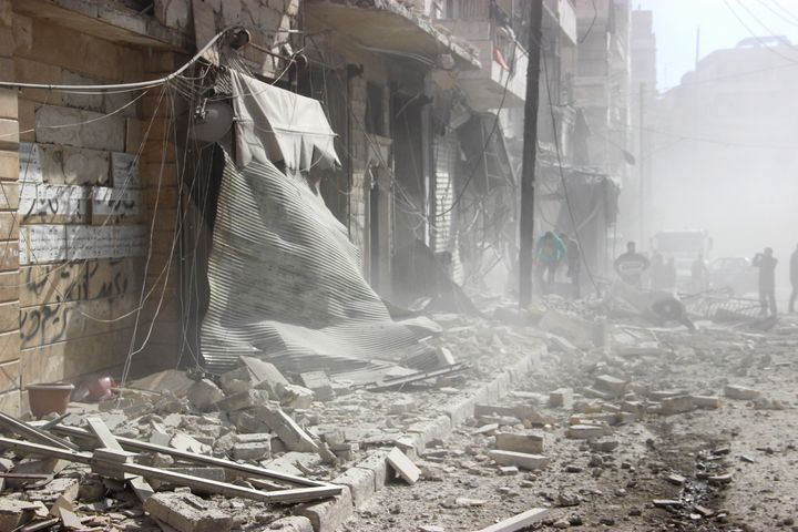 Debris is seen following Russian airstrikes in Aleppo, Syria. Despite its economic woes, Putin has pushed on with aggressive