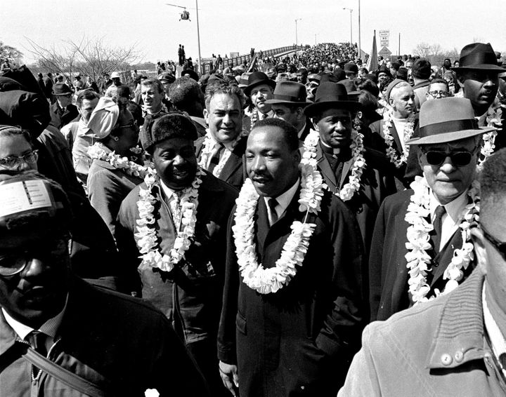 Martin Luther King Jr. leads a march for voting rights across Edmund Pettis Bridge in Selma, Alabama, on March 21, 1965. Stat