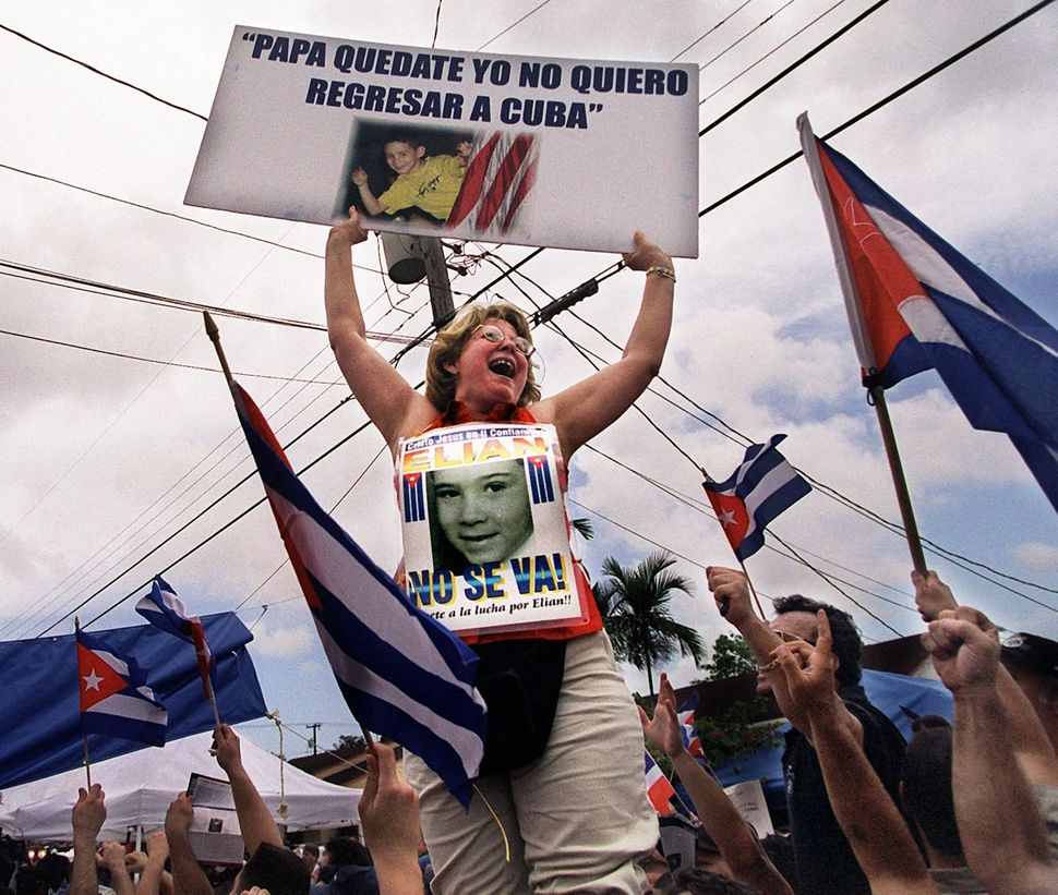 A Woman Demonstrating On Behalf Of Elian Gonzalez Remaining In The United States Is Hoisted Into The Air April 13, 2000 By Fe