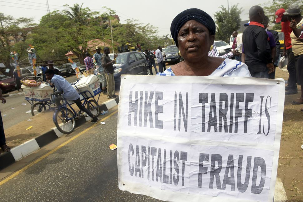 "A woman holds a placard reading ""Hike in tariff is  capitalist fraud"" during a demonstration to protest against the 45 percen"