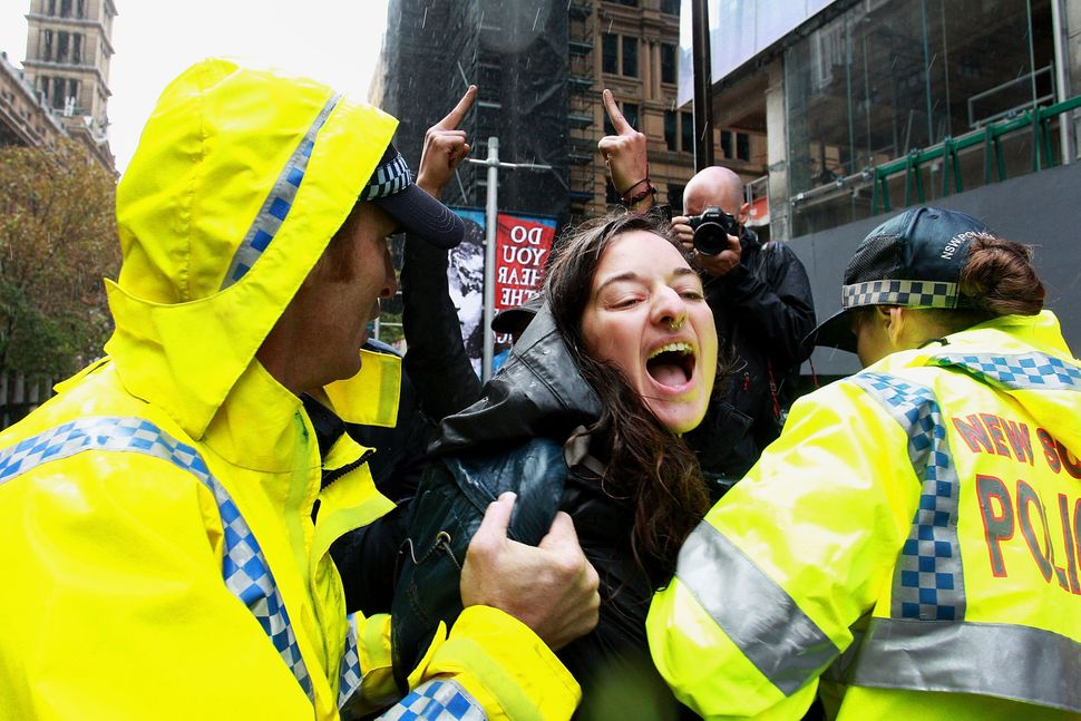 A woman is removed by police from the Martin Place stage after storming the area to speak out against 'Reclaim Australia' pro