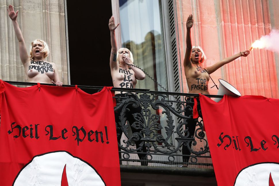 "Topless Femen activists perform the Nazi salute near flags reading ""Heil Le Pen"" as they demonstrate on a balcony against Fra"