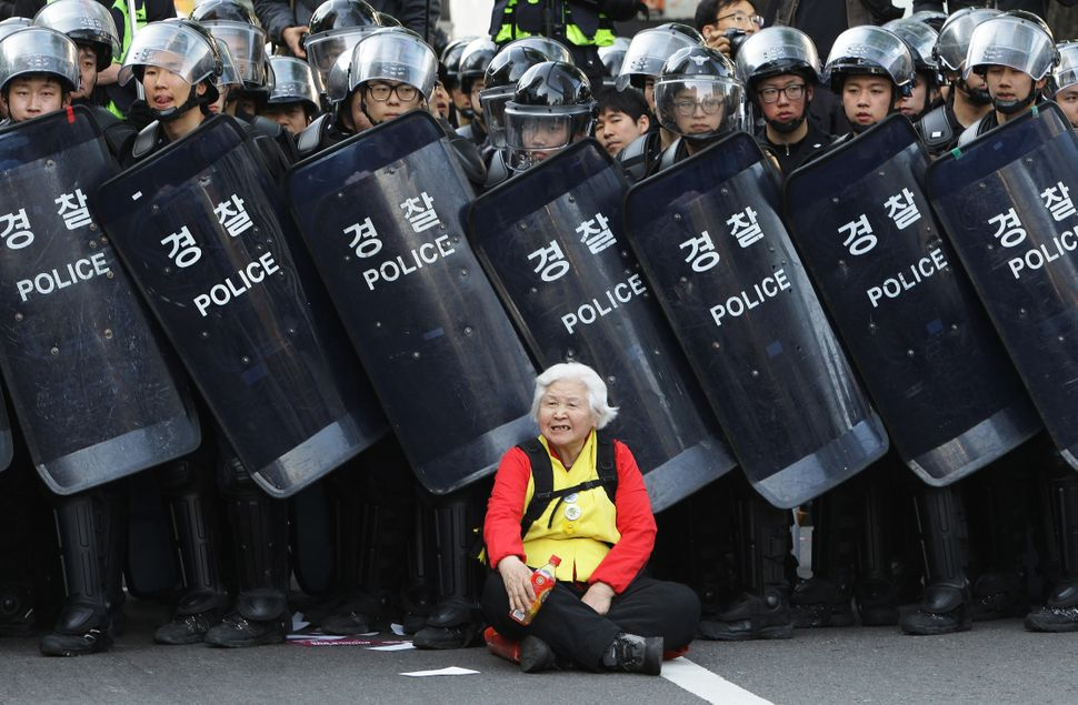 A woman  sits in front of riot police blocking the road to protect protesters during the anti-government  protest on April 24
