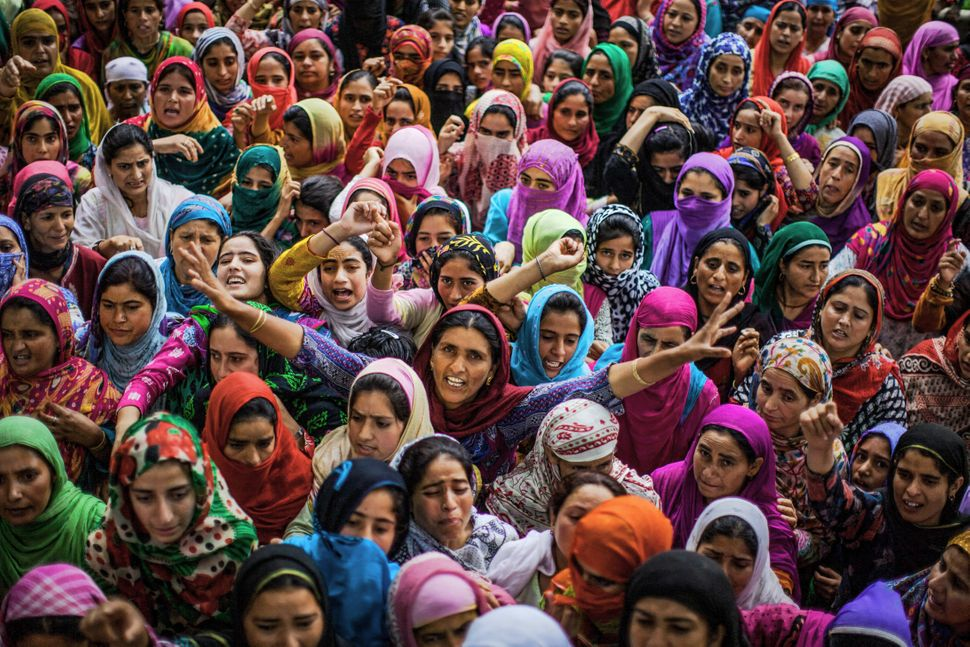 Kashmiri Muslim women shout anti Indian and pro Kashmir freedom slogans as they mourn during the funeral of Bilal Ahmad Bhat,