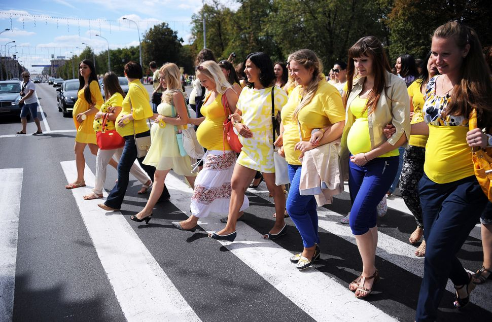 Pregnant women cross a road as they parade in central Minsk on August 30, 2015.