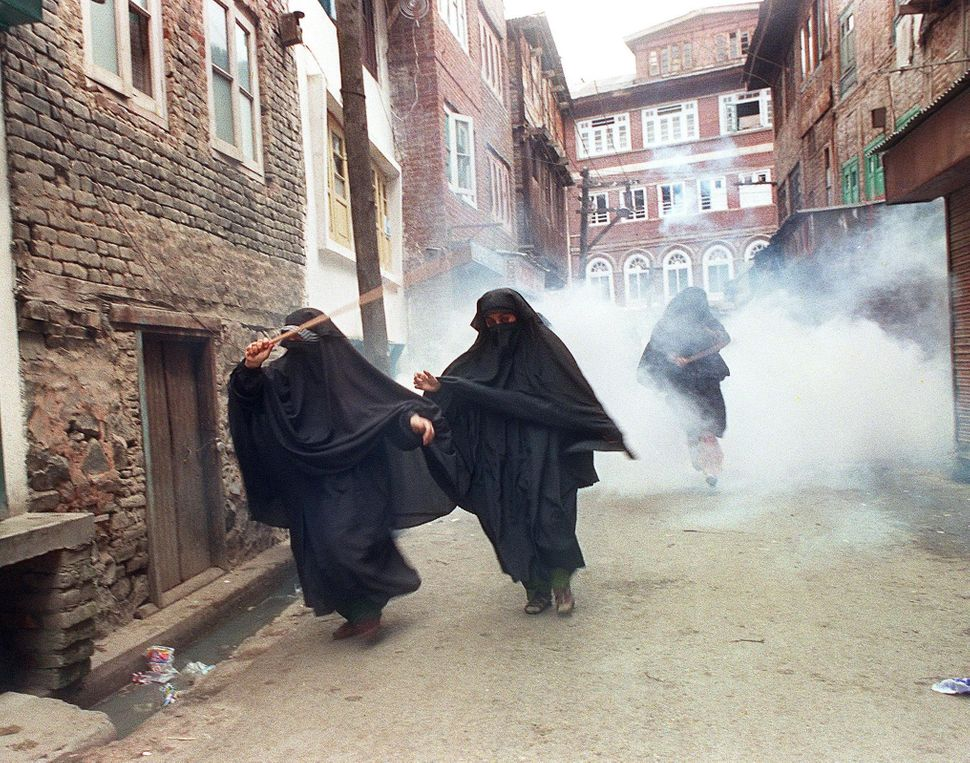 Muslim women in purdah opposed to the state's upcoming assembly elections flee teargas during a demonstration 03 September 19