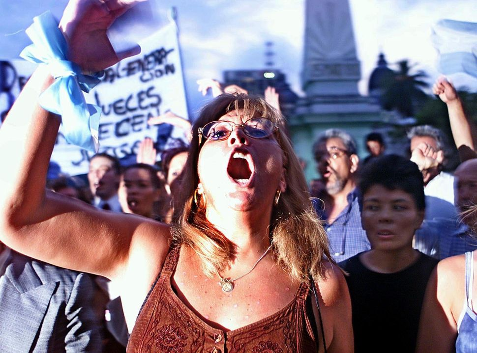 A woman shouts slogans during a nationwide protest against government-imposed restrictions on access to bank accounts and to