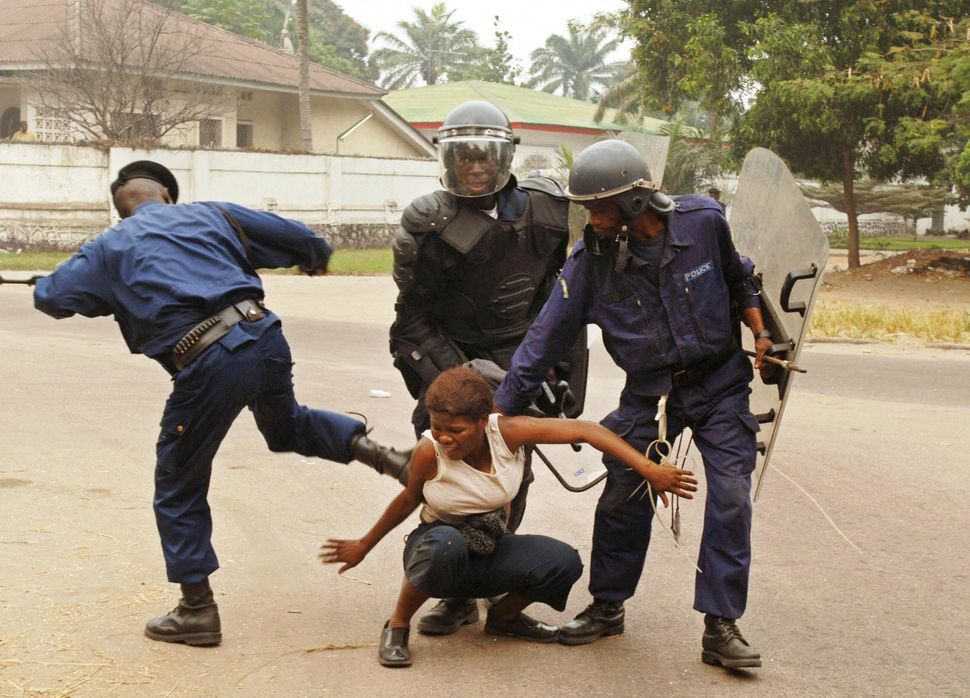 A policeman kicks a woman during a demonstration with a group of the main opposition Union for Democracy and Social Progress