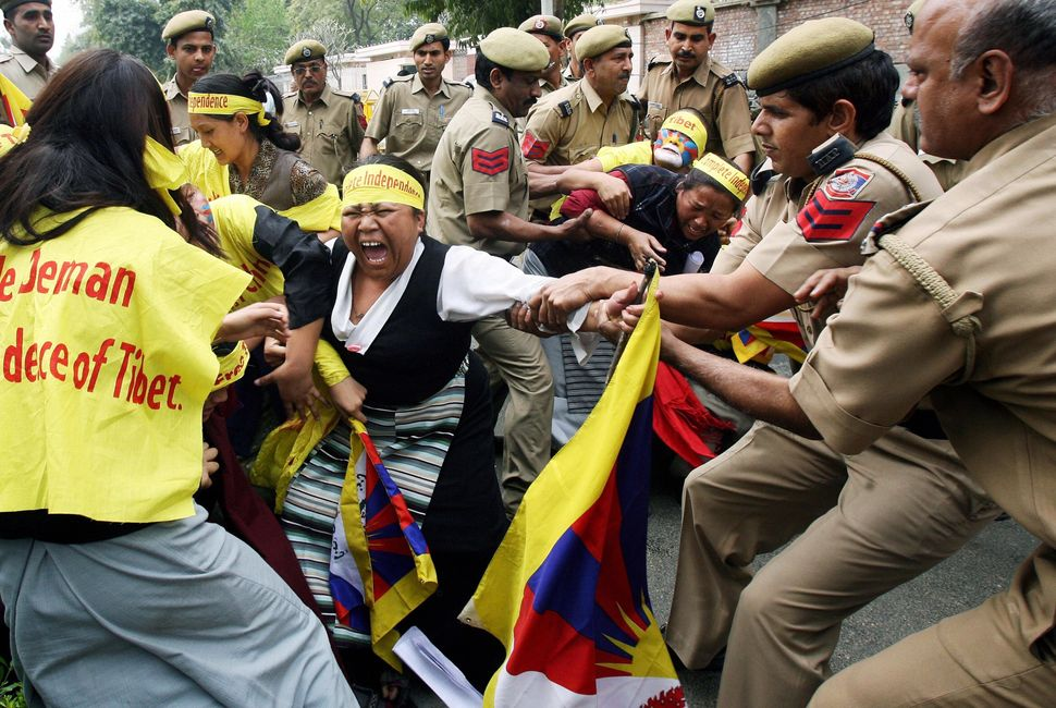 Indian policemen restrain a Tibetan woman during a demonstration at the Chinese Embassy in New Delhi on March 12, 2008 on the