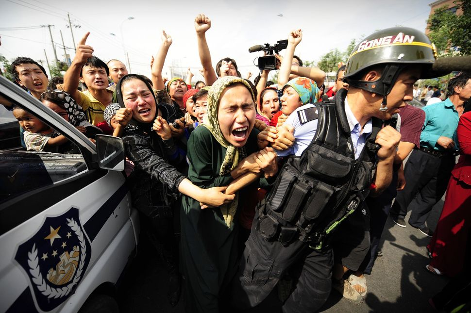 Ethnic Uygur women grab a riot policemen as they protest in Urumqi in China's far west Xinjiang province on July 7, 2009.   P
