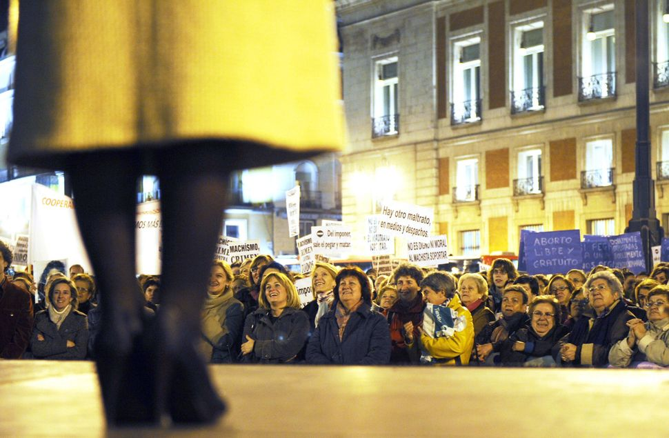 Women display placards during a demonstration to mark the International Day for the Elimination of Violence Against Women in