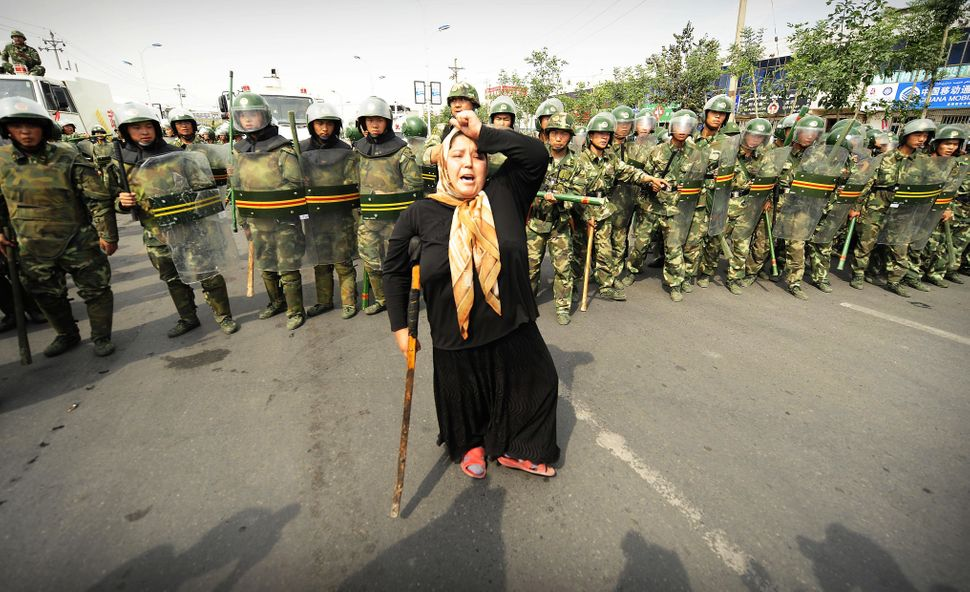 Chinese riot police watch a Muslim ethnic Uighur woman protest in Urumqi in  China's far west